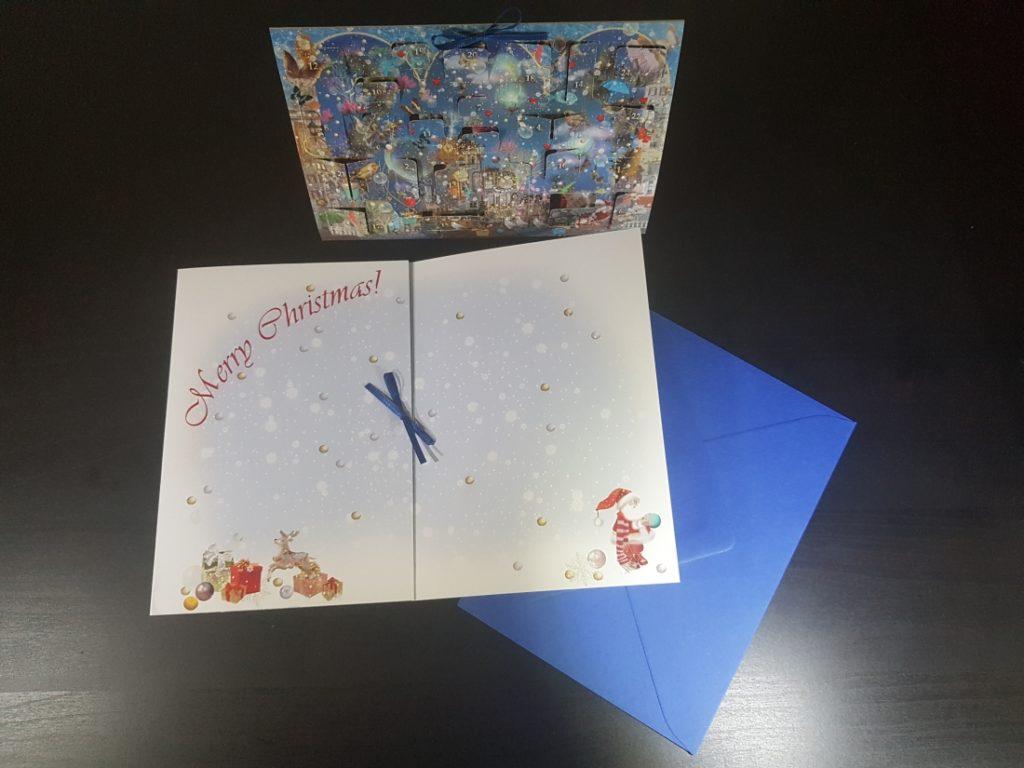 """aufgeklappter Adventskalender mit der Inschrift """"Merry Christmas"""""""